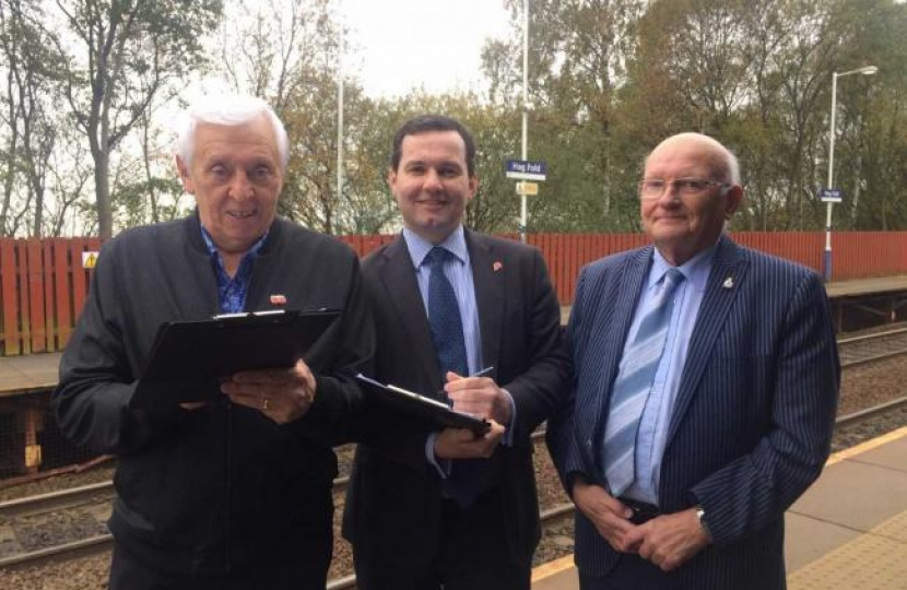 Bolton West MP Chris Green, centre, with a resident signing the petition and chair of The Bridge at Dorset Road Community Centre Norman Bradbury at Hagfold railway station